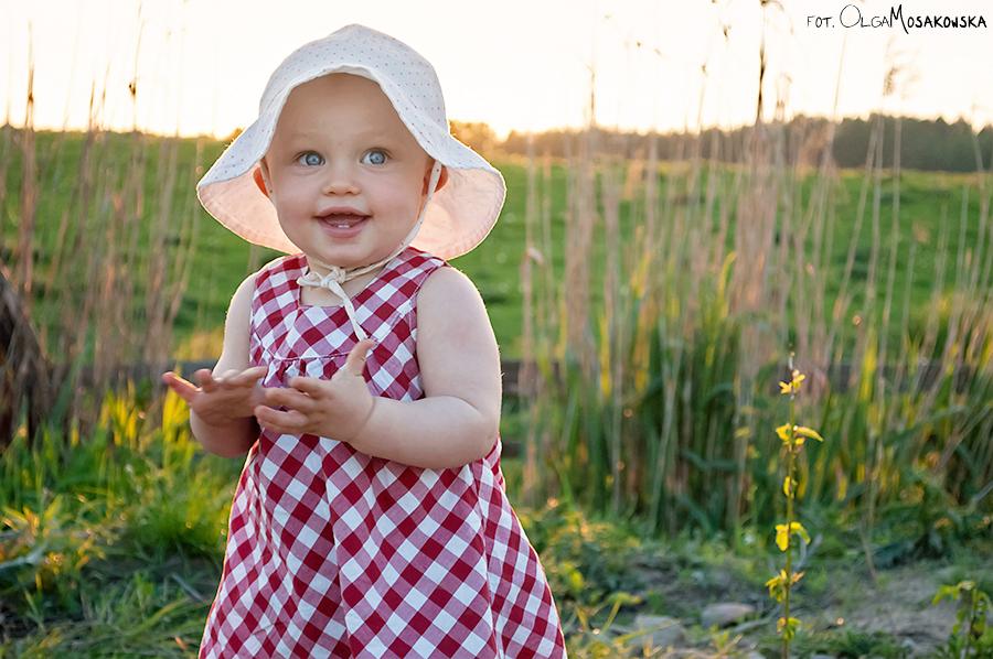 Fotografia dziewczynki w słoneczny dzień, nad stawem w Olsztynie.