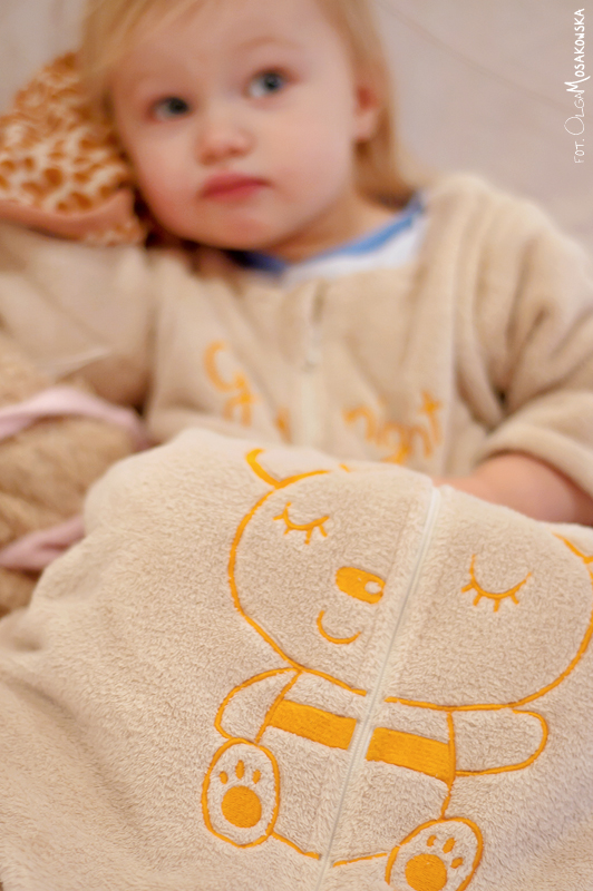 Projekt fotograficzny - Coś pomarańczowego. Zdjęcie małego dziecka w śpiworku.
